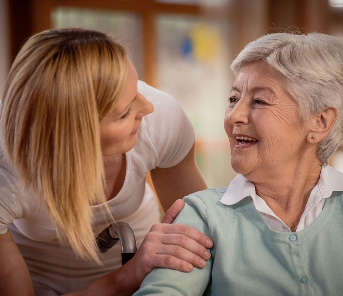Personal care provider assisting older adult with her daily living activities.