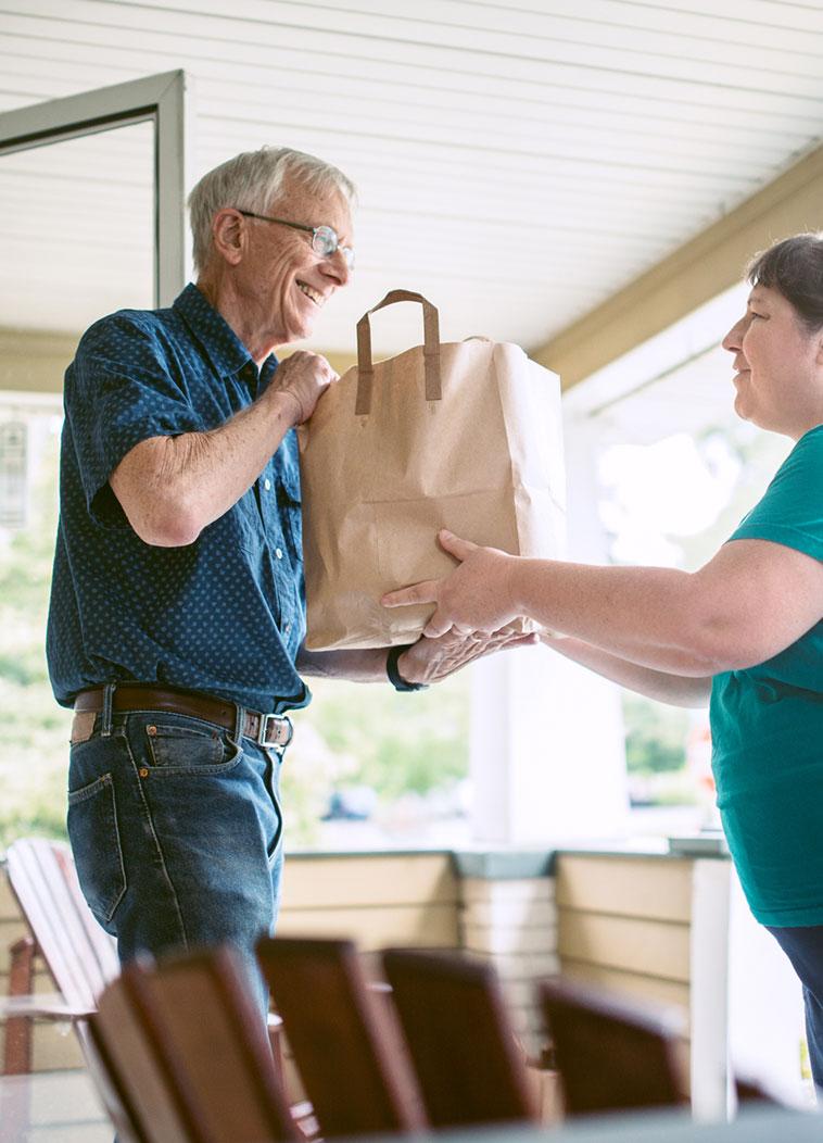 volunteer delivering meals to elderly home