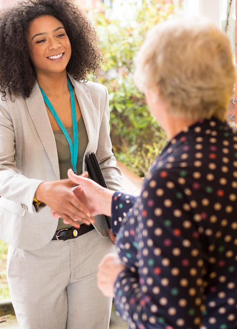 woman shaking elderly woman's hand at door