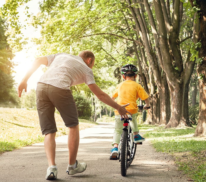 father teaching son to bike