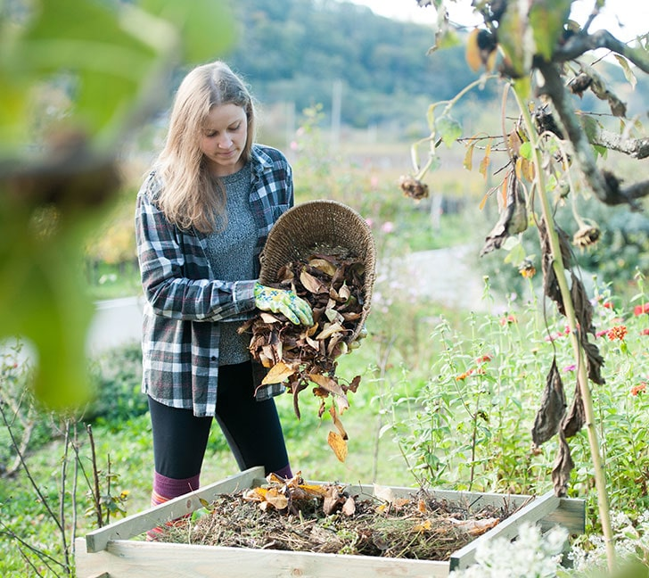 woman composting in backyard