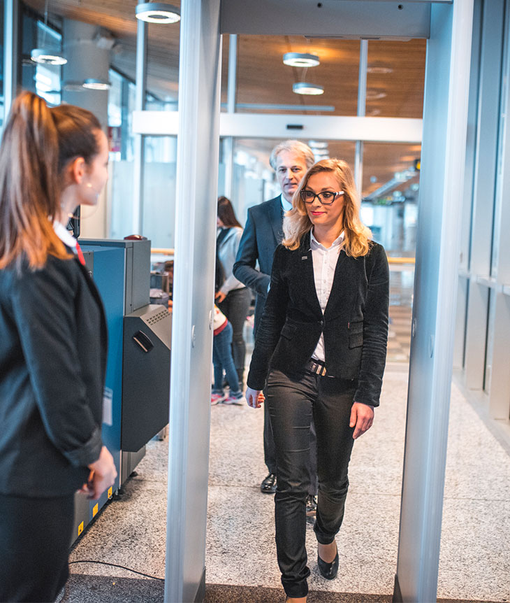 woman walking through metal detector